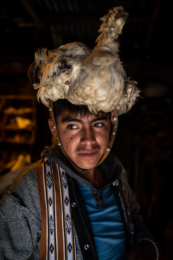 "Before heading to the festival, a participant in ""Quaranwantanna"" costume stands waiting without his mask. Often onsisting of a traditional Peruvian ski mask, leather jacket, riding gear, and a dead bird, this costume is most favoried by young men for it's intimidation factor."