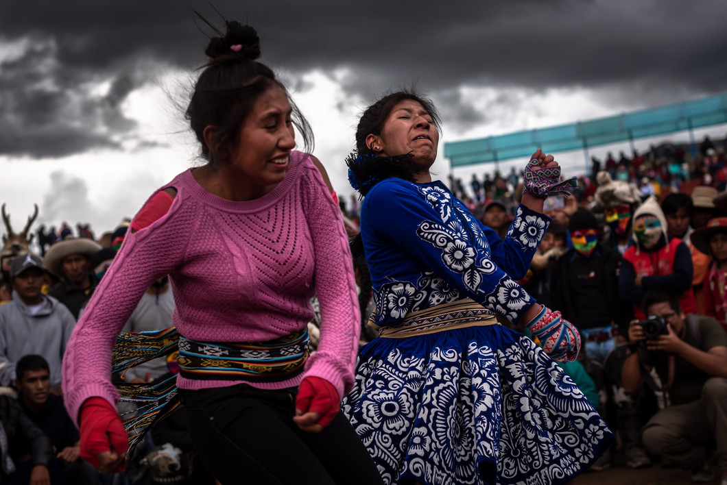 Two women fist fight during the annual Takanakuy fighting festival. Although traditionally prohibited, women today are encouraged by other fighters to participate.
