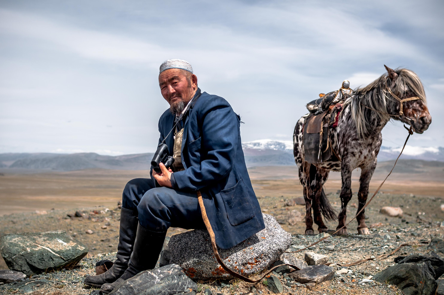 65 year old Saylau, Esen's father, sits with his horse on the lookout for their herd of goats and sheep. Saylau passed the ancient tradition down to his 5 sons.