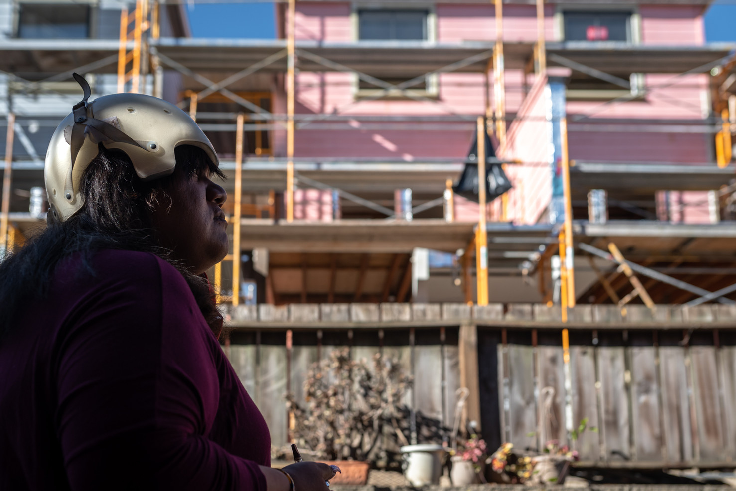 Looming high over their backyard, public housing next door is under renovation. Experiencing memory loss and speech impediment from her ongoing battle with brain lesions, Gaynor's sister Jennifer is required to wear a helmet.