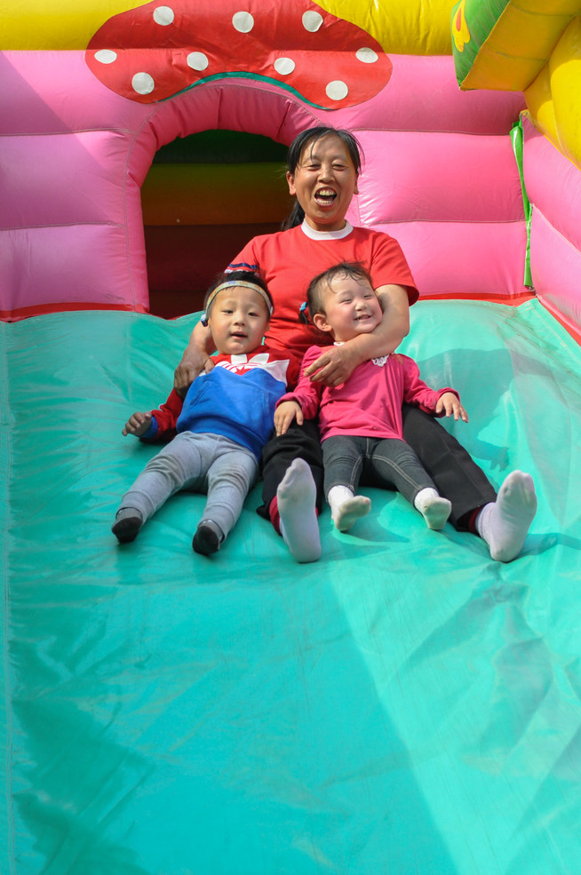 A nanny and her kids go down a bouncehouse slide. Each nanny overlooks the motherly duties of 4 kids.