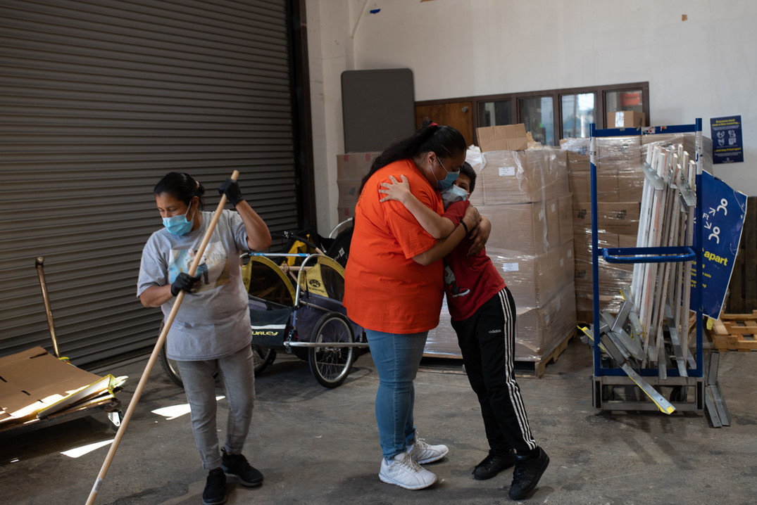 """Embracing a boy volunteering at the Mission Resource hub, Gaynor sets an example for younger community members. """"We need to set an example for our new generation to  volunteer and care for our community."""""""