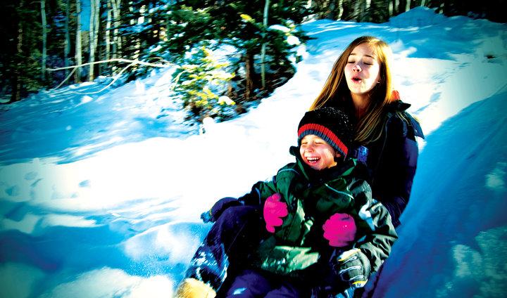 two kids sledding winter snow