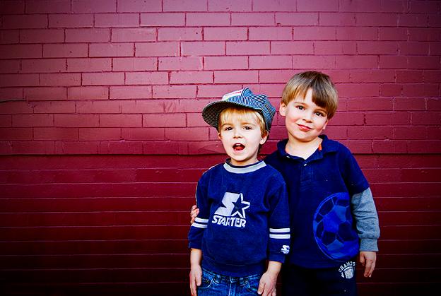 two boys brick wall