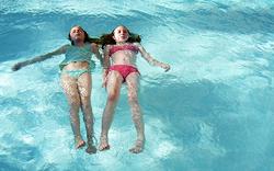 two tweens in pool floating