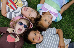 four kids smiling in grass