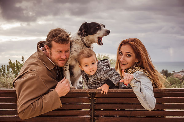 Family of 3 with dog sitting on a bench overlooking the ocean in Perth for a family outdoor photoshoot