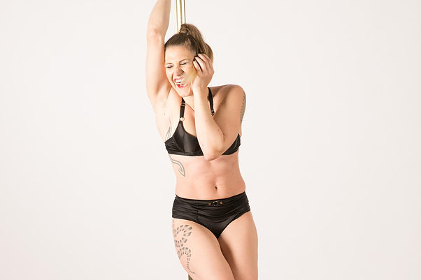 Woman in lingerie during a pole dance shoot laughing and having fun