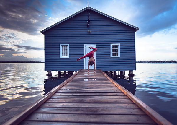 Woman in front of a boat house doing  a handstand for an outdoor yoga photoshoot in Perth