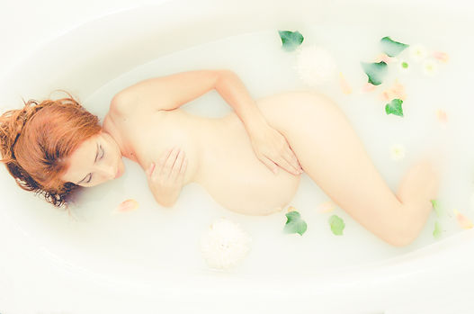 Pregnant woman in a milk bath with flowers and ivy for a styled maternity shoot in Perth