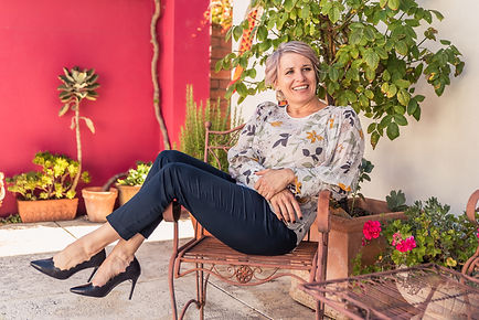 Entrepreneur sitting outside in front of pink wall smiling into the camera