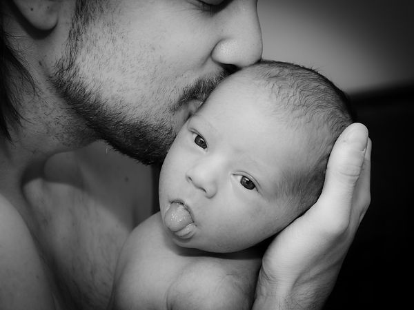 Black and white photo of father holding a newborn baby in his hand giving him  a kiss for a newborn photoshoot in Perth