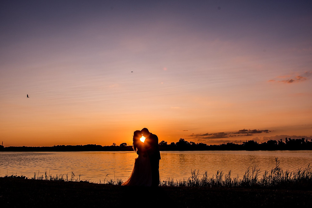 silhouette bride and groom on sunset by the water at thousand acre farm venue for wedding
