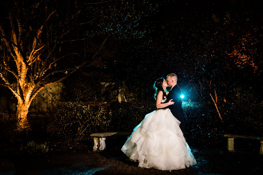 bride and groom at night time at radnor country club kissing in the rain