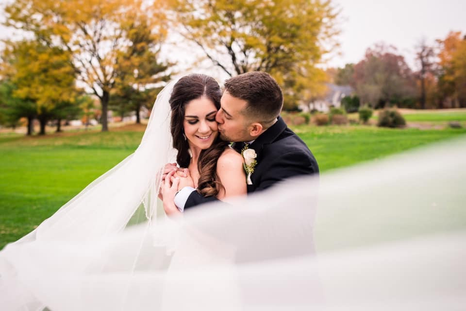 groom kissing bride on the cheek with veil flowing in the air in the fall foliage at country club