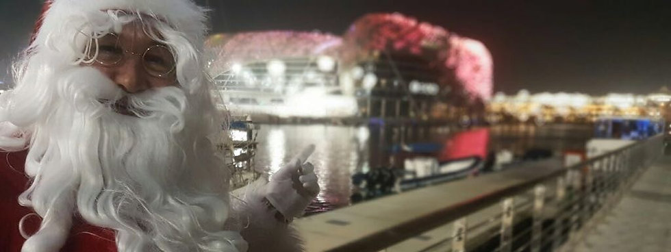 Me a Santa Claus in Abu Dhabi, Yas Marina, Yas Island, with the Viceroy hotel as a background.