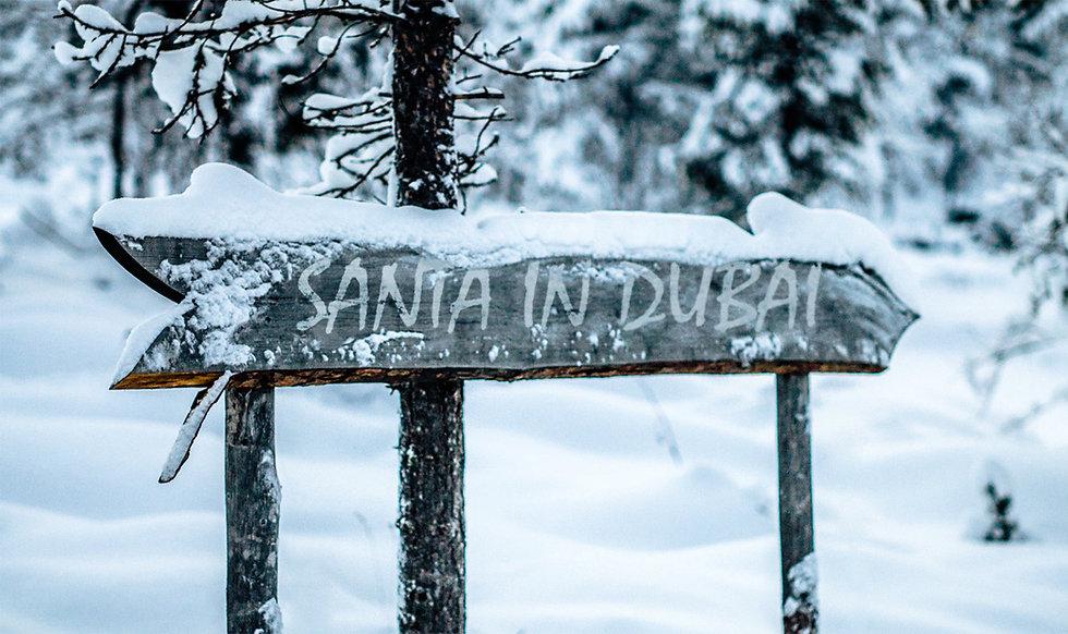 Santa in Dubai arrow signpost with snow. Pointing the way to Dubai Santa Claus.
