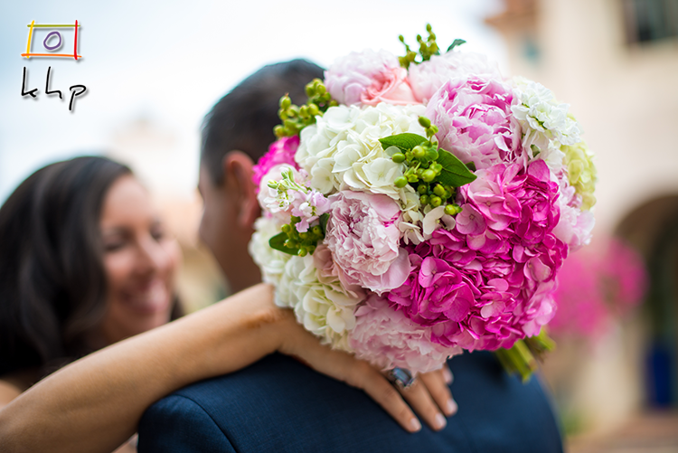 The bride's bouquet as the groom embraces her at Rancho Chiquita in Malibu CA