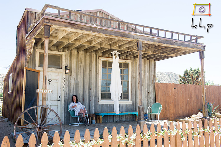 The bride and her gown on the porch of the cottage in Pioneertown CA for a desert wedding