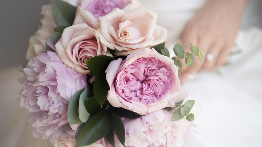 A bride holding her bouquet with peach roses, pink garden roses, eucalyptus and greenery.