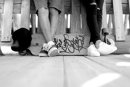 Two people's legs. Leaning against a wood fence or bench, with a skateboard on the ground behind them.