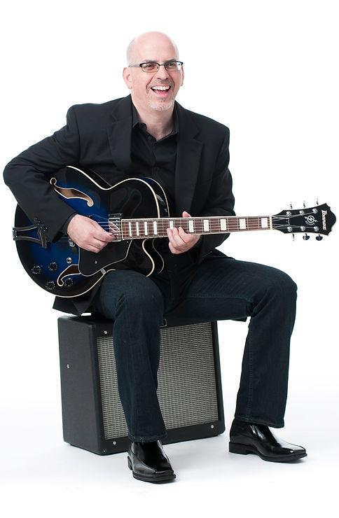 Joe Serio sitting on an amplifier playing guitar