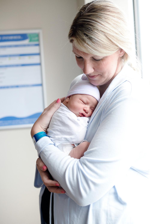 Mom holding newborn baby in hospital