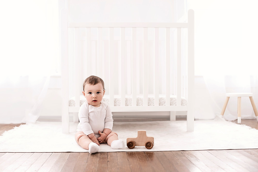 baby rolls sitting on floor in front of crib playing with toy truck