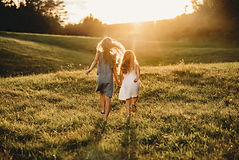 Sisters Running in Field during Sunset Golden Hour
