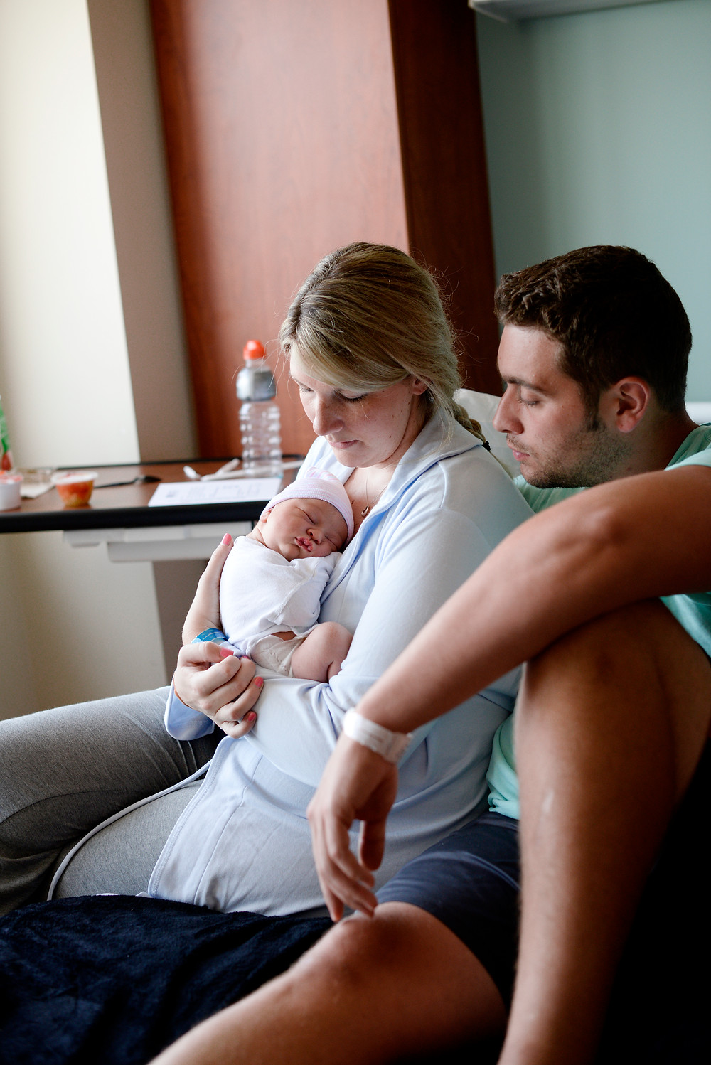 new mom and dad loving new baby boy in hospital bed