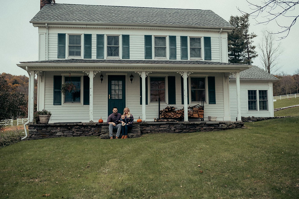 family sitting on front porch farmhouse in the catskills