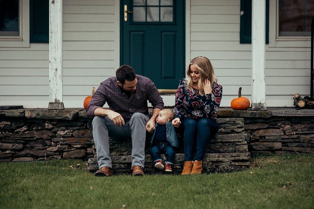 little family on steps in the fall with pumpkins