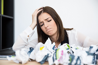 Woman looking upset surrounded by paper