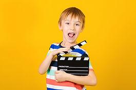 Kid hands holding clapper board for maki