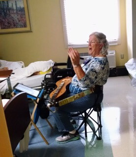 Pat Clark with her dulcimer talking to a patient during a hospital visit.