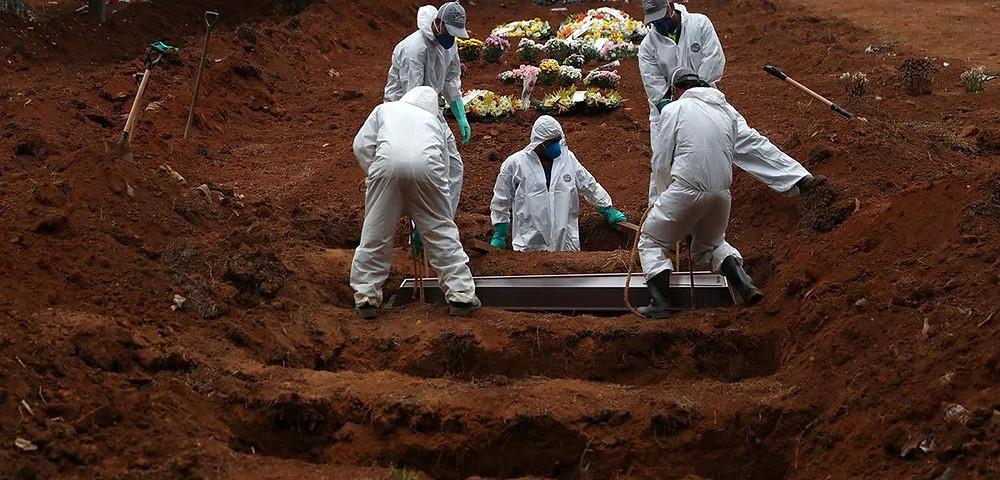 Coveiros com trajes de proteção enterram homem morto pela Covid-19 em cemintério em São Paulo 04/06/2020 (Foto: REUTERS/Amanda Perobelli)