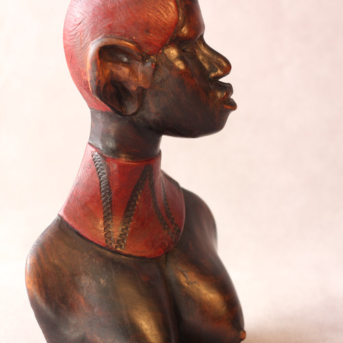 """African Woman Wood Sculpture With an intense look of pride this African woman sculpture represents for us the enduring strength and wisdom of women of color worldwide. It is mostly likely east African, from Tanzania or Kenya, possibly Samburu tribe, based on hair and wide decorative necklace. With its flat back it fits comfortably almost anywhere, creating a mood of unspoken respectful tolerance. The wood is a heavy hardwood, stained and oiled to emphasize women's beautiful bravery. Dimensions (inches): H 12"""" tall W 7-1/2"""" D 3""""  $110"""
