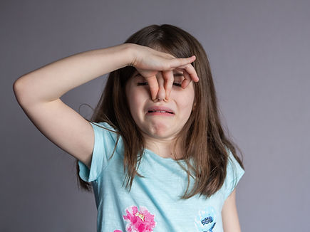 Young girl covering her nose with a bad