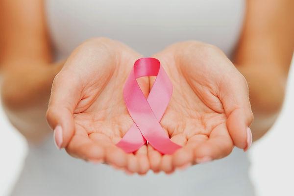 Mãos femininas segurando laço rosa câncer de mama