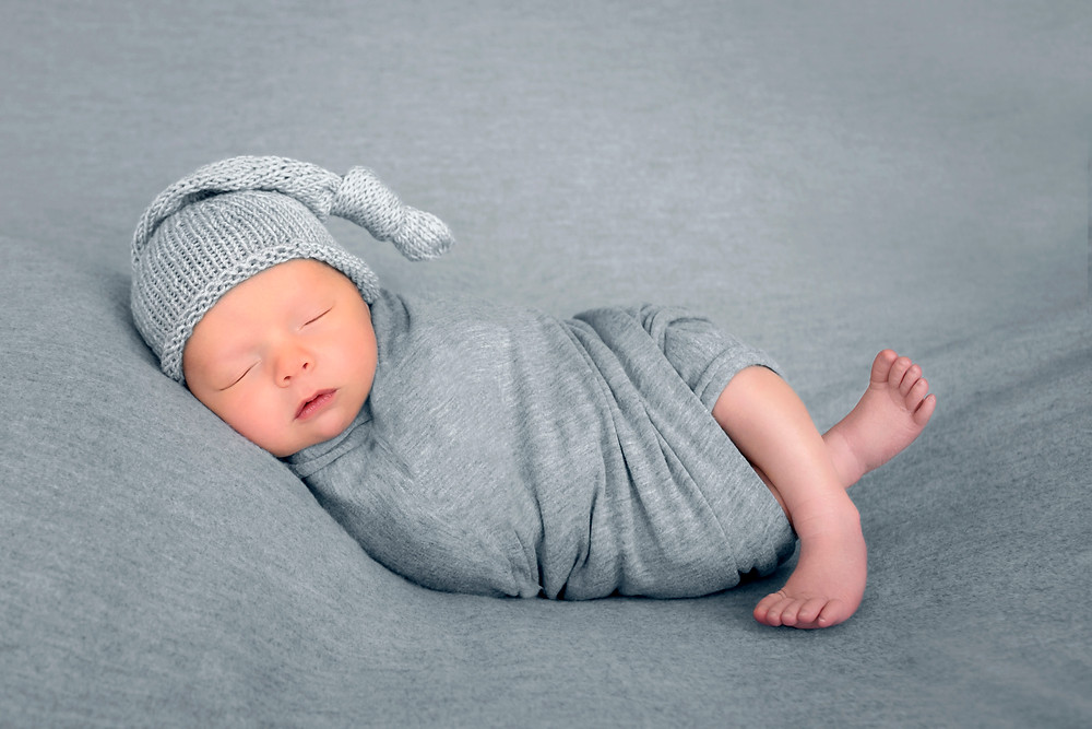 newborn wrapped with sleeping cap