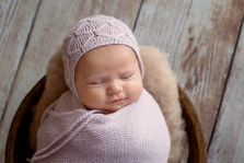 newborn with bonnet smile