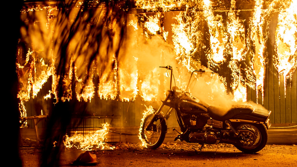 A structure and a motorcycle burn at an RV park during the Woolsey Fire in Malibu, California, November 10, 2018. (Kyle Grillot /The Washington Post/Getty Images)