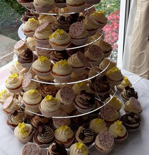 "Assorted cupcakes tower topped with a 6"" cake"