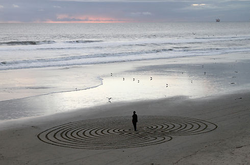 Man meditating in labyrinth maze on beac