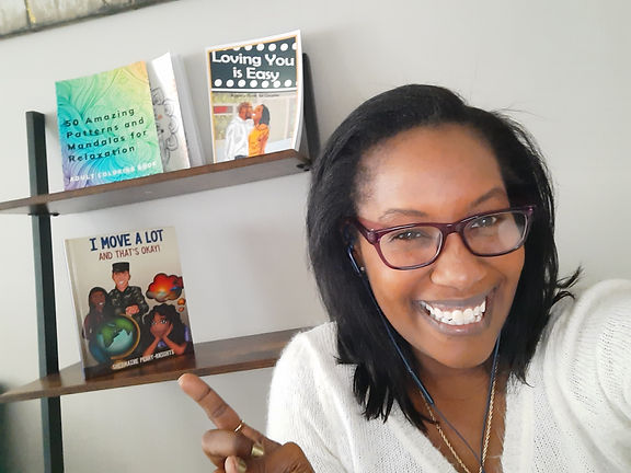 This is Shermaine Perry-Knights posing with 3 of her books.