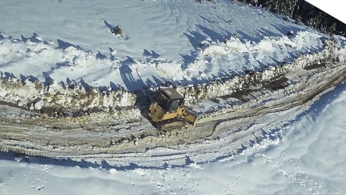 Aerial photo of Snow Plow Truck Cleaning Mountain Road (
