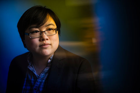 Photo: Headshot of Lydia Brown, young East Asian person, with stylized blue and yellow dramatic background. They are looking in the distance and wearing a plaid shirt and black jacket. Photo by Adam Glanzman.