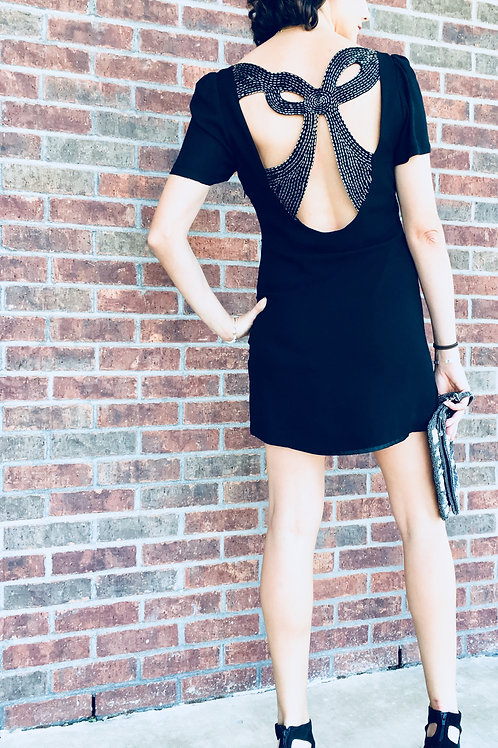 Butterfly back dress, spiked ankle peekaboo boots, blingy clutch