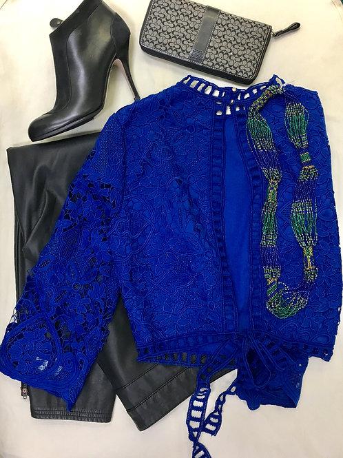 Black leather pants, blue lace open back shirt, black ankle boots