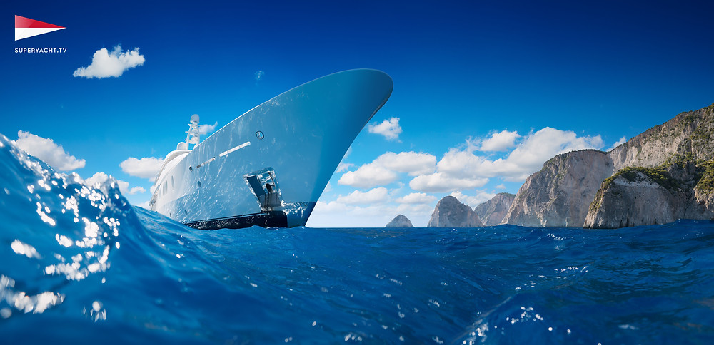 Luxury Yacht on the sea taken from water with mountains in backg
